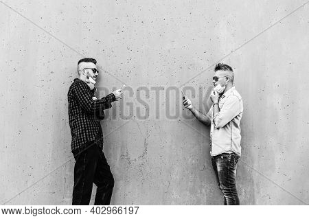 Hipster Men Facing Each Other Using Mobile Phones While Keeping Social Distance And Wearing Face Med