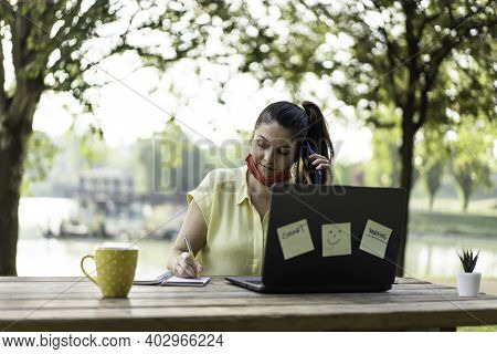 Young Woman Wearing Open Face Mask Calling With Smartphone While Working With Laptop Outdoors - Smil