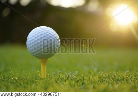 Golf Ball On Tee In Beautiful Golf Course At Sunset Background. White Golf Ball On Tee On Green Gras