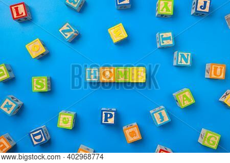 Home. Wooden Colorful Alphabet Blocks On Blue Background, Flat Lay, Top View.