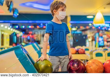 Boy Playing Bowling With Medical Masks During Covid-19 Coronavirus In Bowling Club