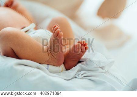 New Born Baby Feet On White Blanket In Hospital