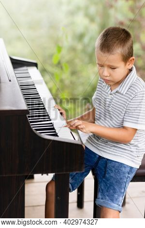 Cute lttle boy playing piano outdoor