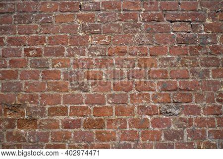Brick texture from old stone. 18th century brick wall. Old burnt brick masonry. Shooting details clo