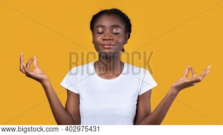 Peaceful African American Woman Meditating With Eyes Closed Relaxing Posing On Yellow Studio Backgro