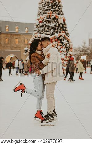 Beautiful Couple In Love. Young Couple Skating At A Public Ice Skating Rink Outdoors. Amazing Winter