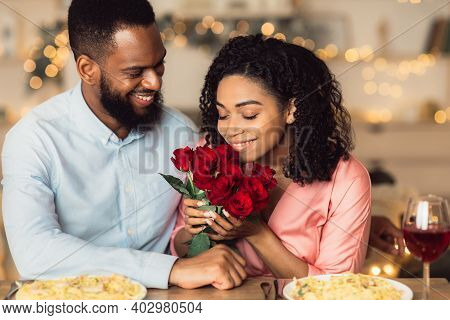 Greeting With Holidays. Happy Beautiful Black Girlfriend Receiving Bouquet Of Red Roses From Her Smi