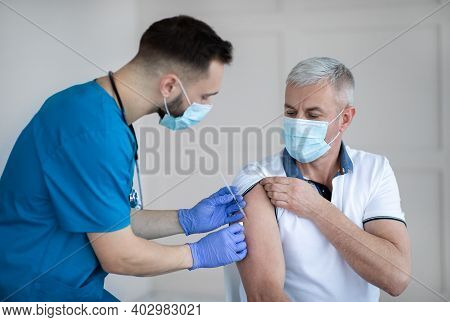 Professional Doctor Or Nurse Giving Covid-19 Vaccine Injection To Senior Patient At Clinic. Mature M