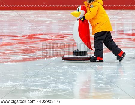 A Child In A Bright Yellow Jacket Learns To Skate On An Ice Rink Holding On To An Assistant, A Toy P