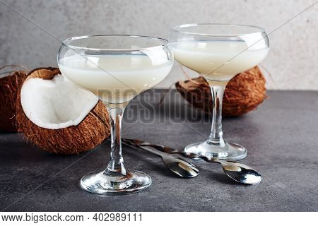 Pina Colada Cocktail In A Glass And Coconut Halves.