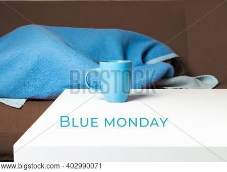 Blue Monday Concept. There Is A Blue Mug On The Table, In The Background Is A Girl Under A Blue Blan