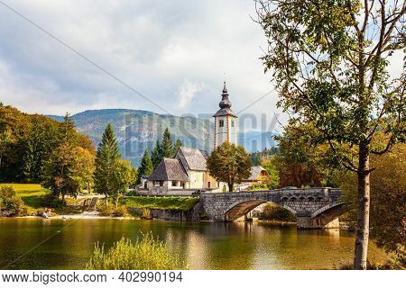Picturesque shores of Lake Bohinj. Magnificent alpine lake of glacial origin in the Julian Alps. Slender bell tower and old stone bridge. Slovenia, Central Europe