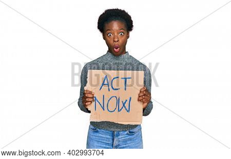 Young african american girl holding act now banner scared and amazed with open mouth for surprise, disbelief face