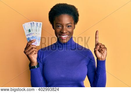 Young african american girl wearing doctor uniform holding 50 colombian pesos smiling with an idea or question pointing finger with happy face, number one