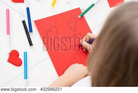 The Child Draws A Postcard For The Holiday Of Mother's Day. Girl Writes On Red Paper I Love You Mom
