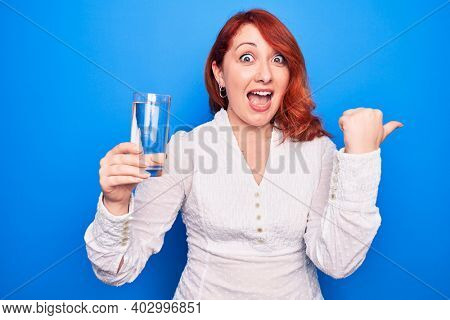Young beautiful redhead woman drinking glass of water over isolated blue background pointing thumb up to the side smiling happy with open mouth