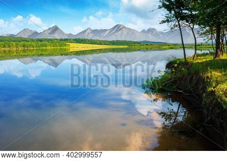 Composite Landscape Of Mountain Lake In Summer. Beautiful Nature Scenery On A Sunny Morning. Sky And