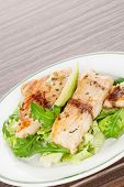 Culinary seafood eating. Grilled fish fillet with fresh rocket and lettuce salad on plate isolated on brown background. poster