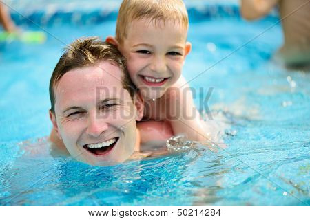 Young Father And Little Son Swimming In Pool