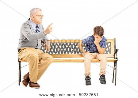 Angry grandfather shouting at his sad nephew, seated on a wooden bench, isolated on white background