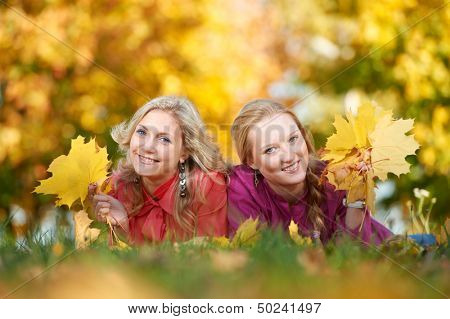 Two Smiling young attractive women with autumn maple leaves in park at fall outdoors
