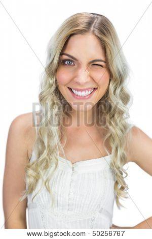 Smiling blue eyed model on white background winking at camera