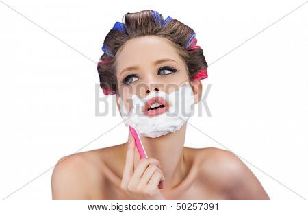 Pensive woman in hair curlers posing with razor on white background