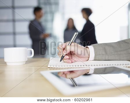close-up of male's hand writing on notepad with people talking in background. poster