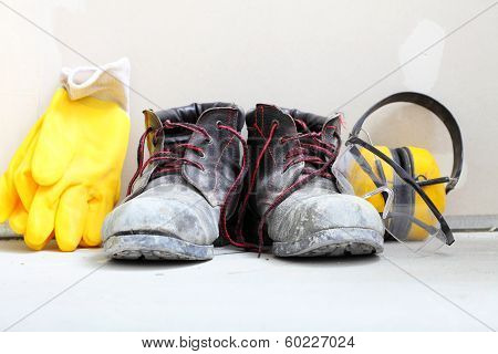 Renovation at home. Construction equipment tools work boots yellow protective noise muffs gloves in building site. poster