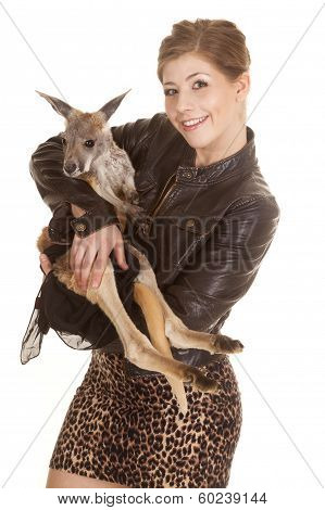 a woman in her leather jacket holding on to her pet kangaroo smiling. poster