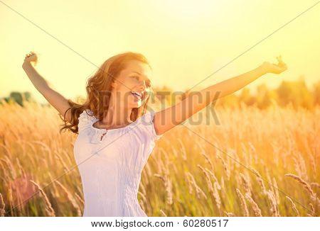 Beauty Girl Outdoors enjoying nature. Beautiful Teenage Model girl in white dress running on the Spring Field, Sun Light. Glow Sun. Free Happy Woman. Toned in warm colors.