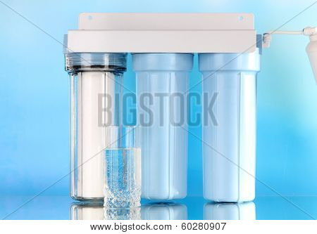 Filter system for water treatment with glass on blue background