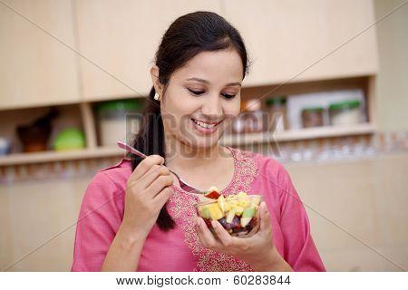 Young Woman Eating Fruit Salad