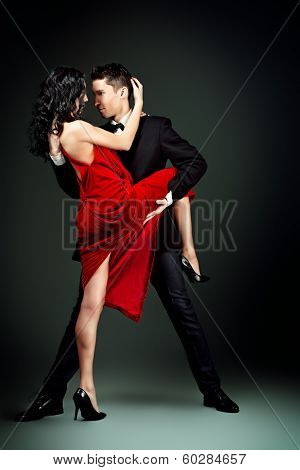Beautiful young couple in love dancing passionate dance. Studio shot.