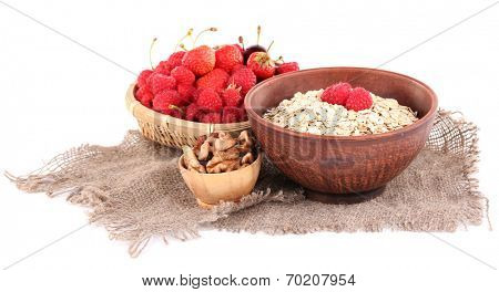 Wooden bowls of berries on sackcloth isolated on white