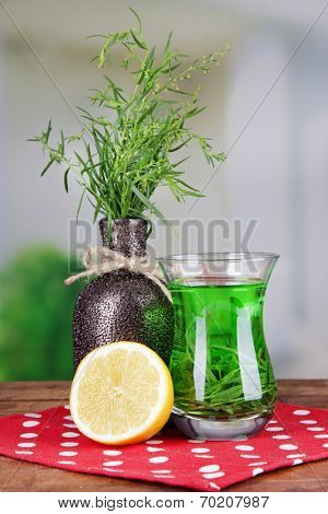 Estragon drink with lemon on wooden table on bright background