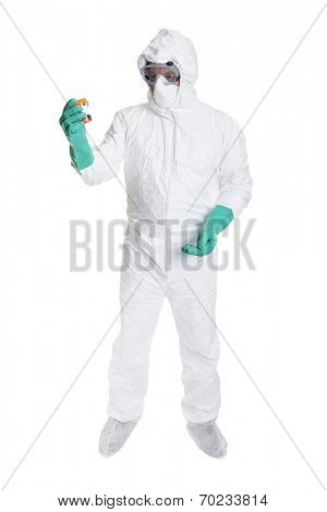 A scientist in a bio hazard suit looking at a sample of body fluid, shot on a white background.
