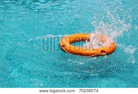 Orange Life Buoy Splash Water In The Blue Swimming Pool