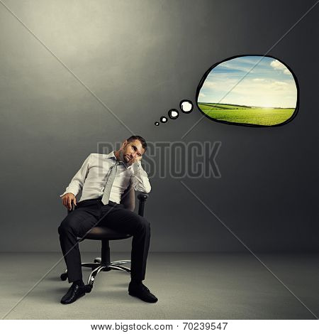 bored businessman sitting on the chair with speech bubble and thinking about rest over grey background