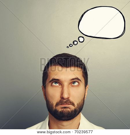 portrait of foolish man with empty speech balloon over grey background