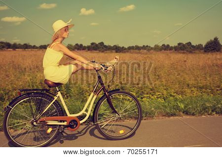 Young girl having fun riding a retro style bike in the countryside.