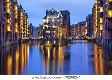 House and two brides illuminated at evening in old warehouse district (Speicherstadt) Hamburg Germany poster