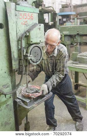 Senior worker drills bores on detail by driller