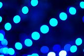Defocused image of blue bulbs. Background on black poster