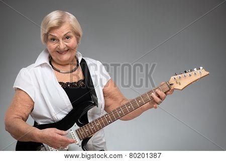 Elderly woman holding the guitar