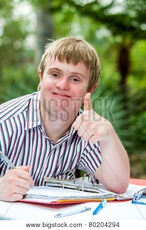 Handicapped Boy Doing Thumbs Up At Desk Outdoors.