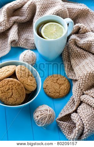 A Cup Of Tea With Lemon, Biscuits, Beige Knitted Blanket  Lie On Blue Tray
