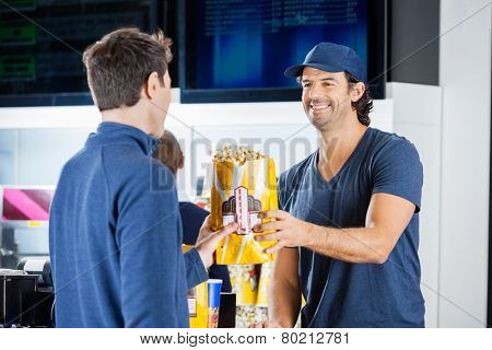 Smiling male seller giving popcorn paperbag to man at cinema concession stand