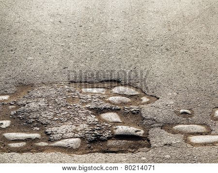 Cutting Of An Old Road With Cracked Asphalt And A Gully In The Center Of Cobblestones