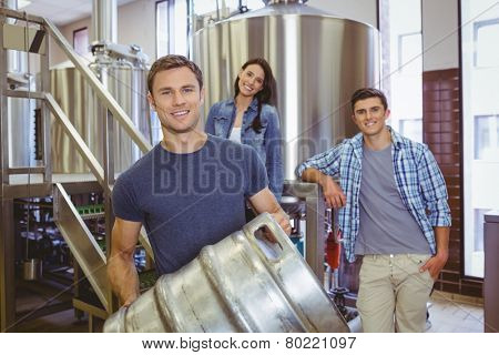 Young man holding keg with these colleagues behind him in the factory